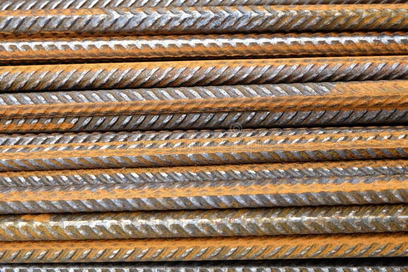 En closeup av den rostiga horisontellt staplade ståluppdelningsförstärkningen bommar för rebaren arkivbilder