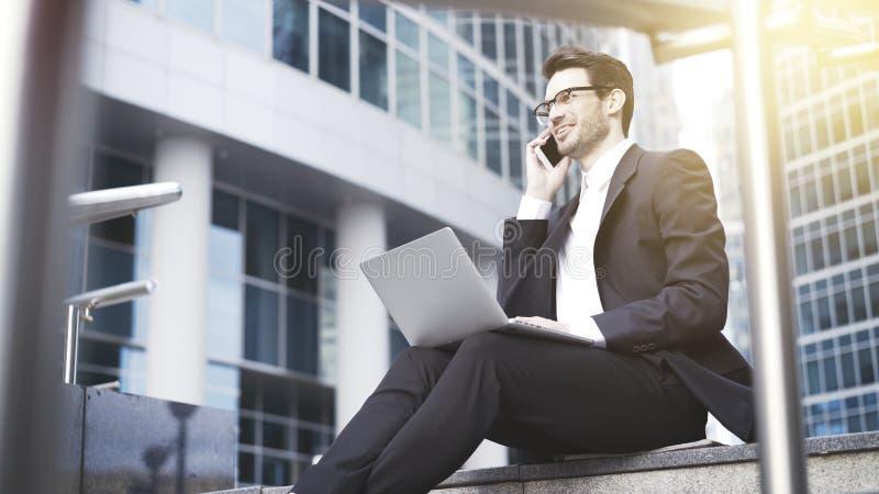 En closeup av den unga lyckliga affärsmannen med bärbara datorn som har en appell royaltyfri bild