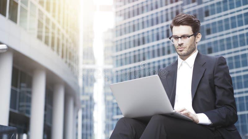 En closeup av den unga stiliga affärsmannen med bärbara datorn utanför arkivfoto