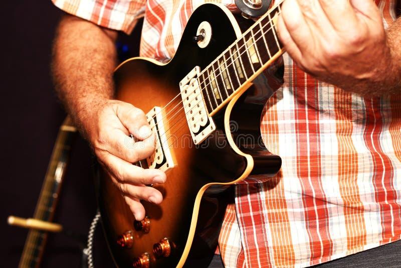 En closeup av en man som spelar en elektrisk gitarr arkivfoto