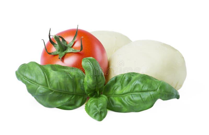 En closeup av Mozzarellaostbollar med nya basilikasidor och tomater på en vit bakgrund royaltyfri foto