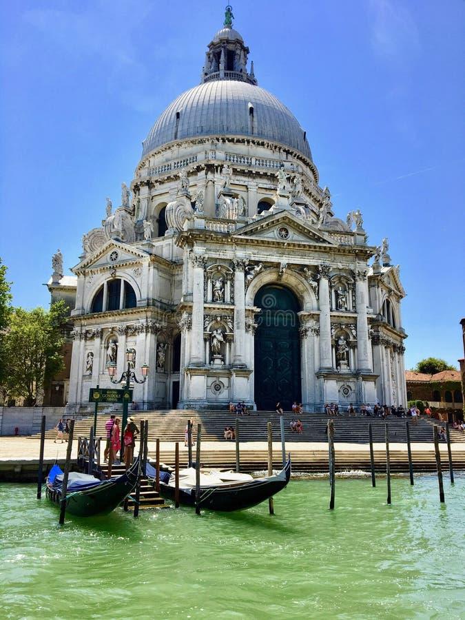 En closeupsikt från Grand Canal av Santa Maria della Salute med två gondoler framme royaltyfria foton