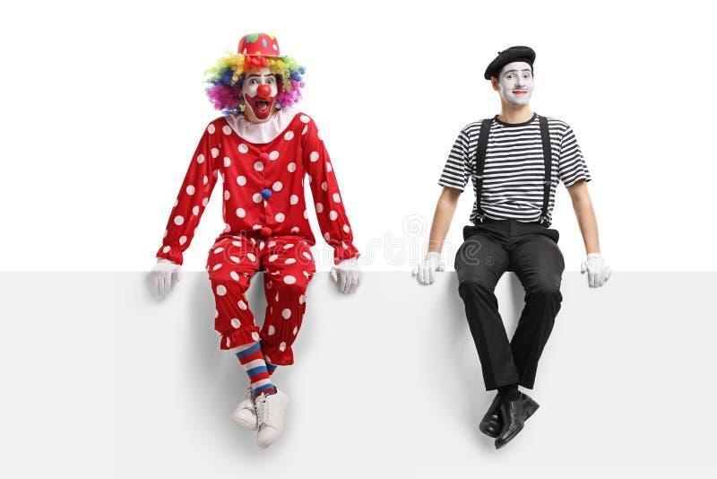 En clown och en fars som sitter på en panel royaltyfria bilder