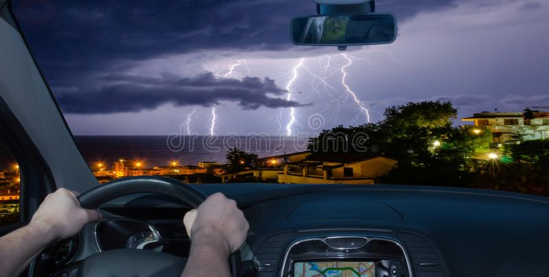 En conduisant une voiture vers une foudre fulminez au-dessus de la mer images libres de droits