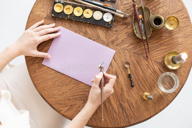 En copywriter skriver en berättelse En hand rymmer en bläckpenna framme av ett tomt ark Fritt avst?nd f?r text slapp fokus fotografering för bildbyråer