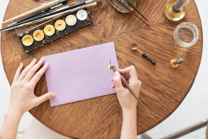 En copywriter skriver en berättelse En hand rymmer en bläckpenna framme av ett tomt ark Fritt avst?nd f?r text slapp fokus royaltyfri foto