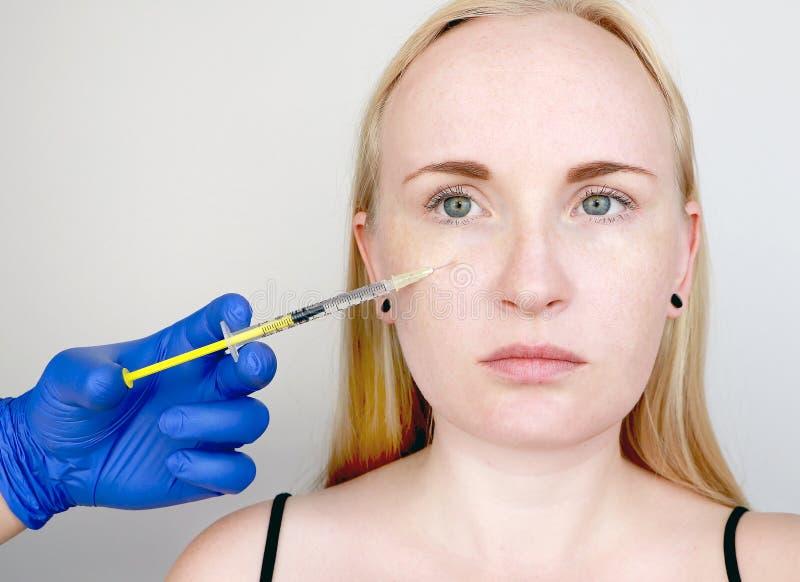En cosmetologist bär ut ett tillvägagångssätt - en injektion in i framsidan av en ung kvinna Skönhetinjektioner, mesotherapy som  arkivbilder