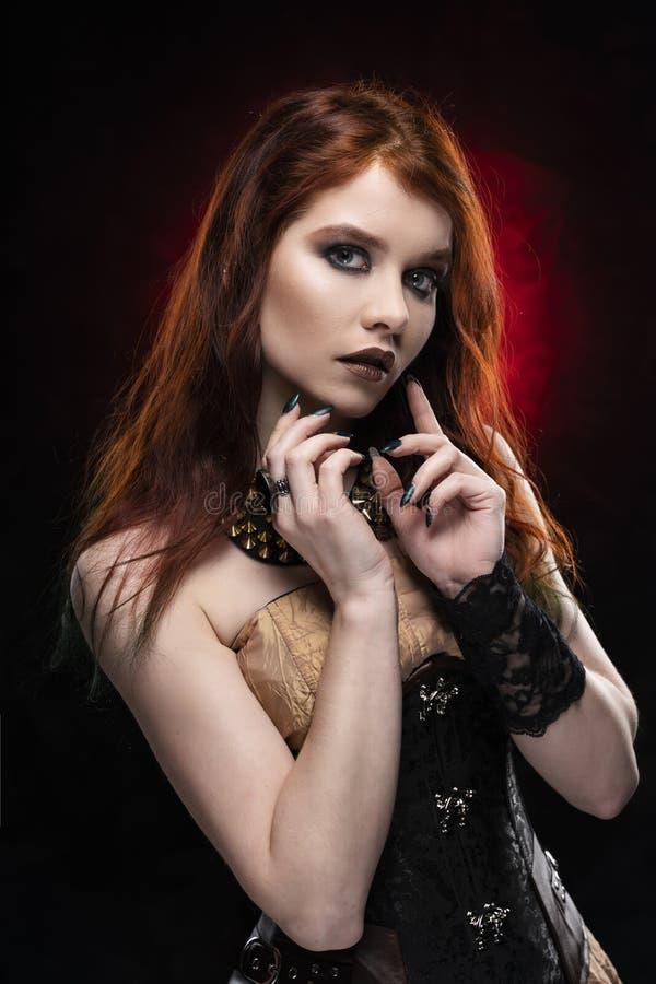 En cosplay flicka för härlig fundersam rödhårig man som bär enstil steampunkklänning och korsett Stående svart red arkivbild
