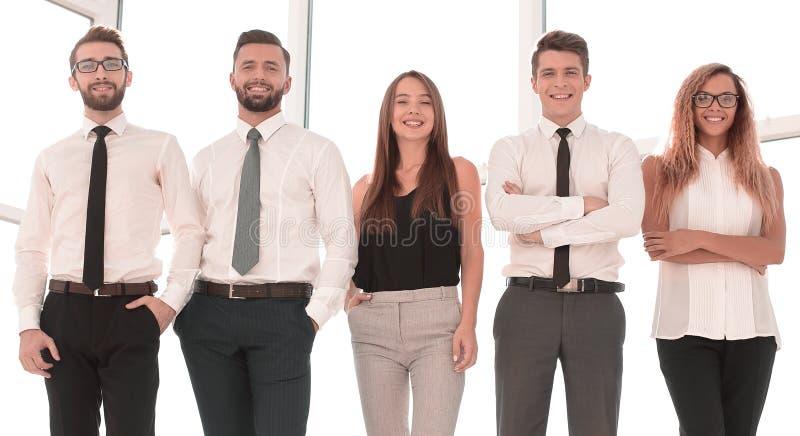 En crecimiento completo equipo moderno del negocio que se coloca en una oficina brillante foto de archivo
