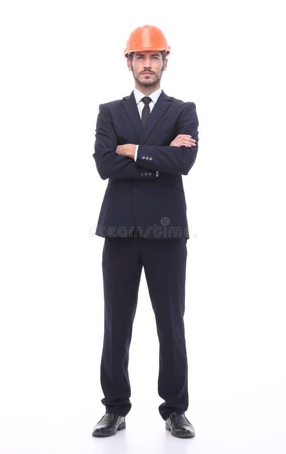 En crecimiento completo un hombre de negocios serio en un casco protector imagen de archivo