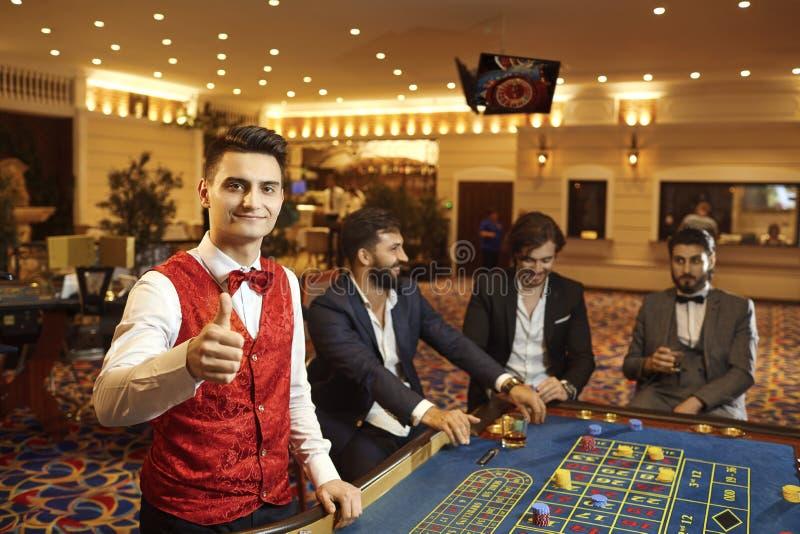 En croupier arbetar på en pokerroulett i en kasino royaltyfria bilder