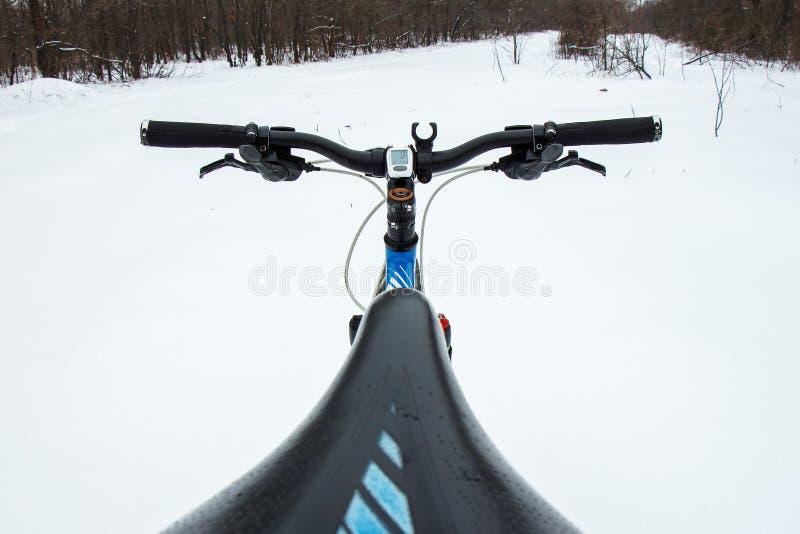 En cykel på bakgrunden av en snöig väg Vinterytterlighetaffärsföretag och lopp Vinterytterlighetaffärsföretag och lopp royaltyfria bilder