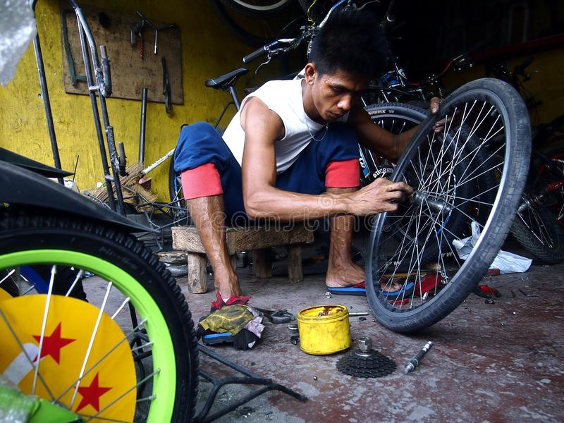 En cykelreparationsman fixar ett gummihjul på ett cykellager arkivbild