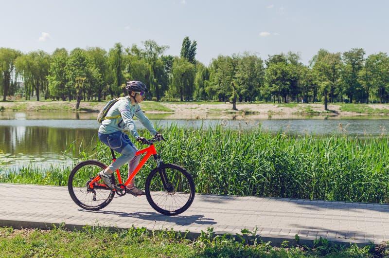 En cyklist i en hjälm som rider en cykelbana vid floden arkivbild
