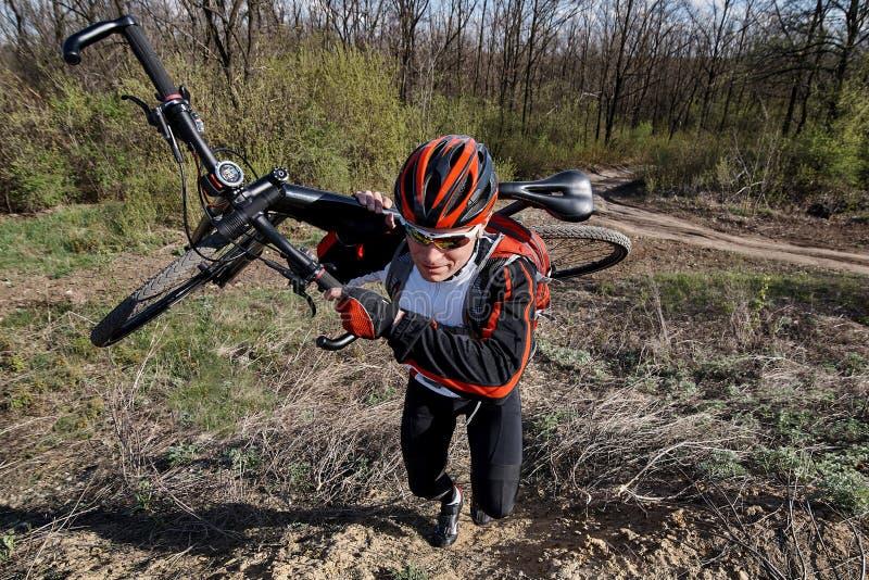 En cyklist i sportswear med en cykel royaltyfria foton