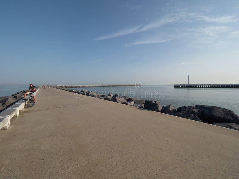 En cyklist på den västra vågbrytaren i Ostend arkivfoton