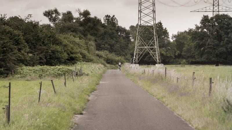 En cyklist passerar en hög spänningspylon på en väg i ängarna royaltyfria foton