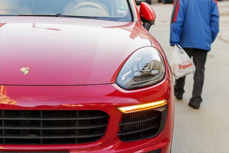 En dåligt klädd hög man går ner gatan förbi en röd Porsche bil Begrepp av lyx och armod Kontrast av armod och royaltyfri fotografi