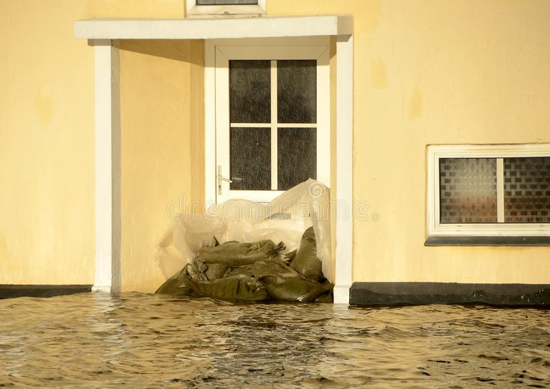 En dörr som blockeras med sandsäckar, tack vare en stormsvallvåg arkivfoton
