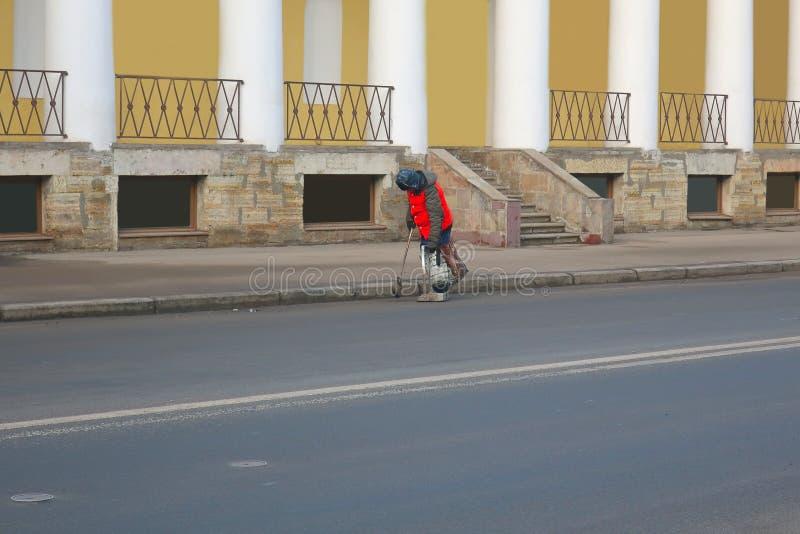 En dörrvakt i en orange väst sopar gatan royaltyfria bilder