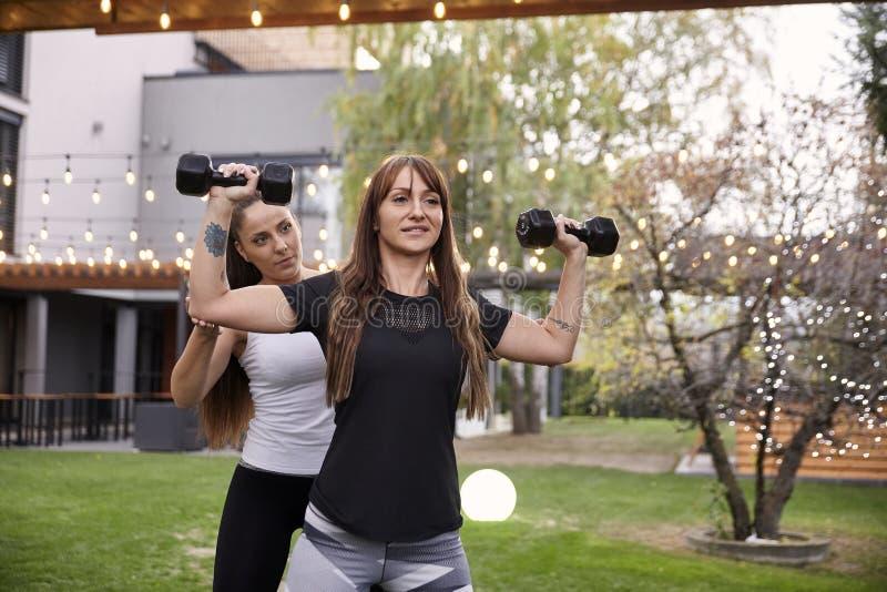 En dam, 20-29 gamla år, hjälper en annan dam hur man gör den övning med vikter i en trädgård av ett utsmyckat hus fotografering för bildbyråer