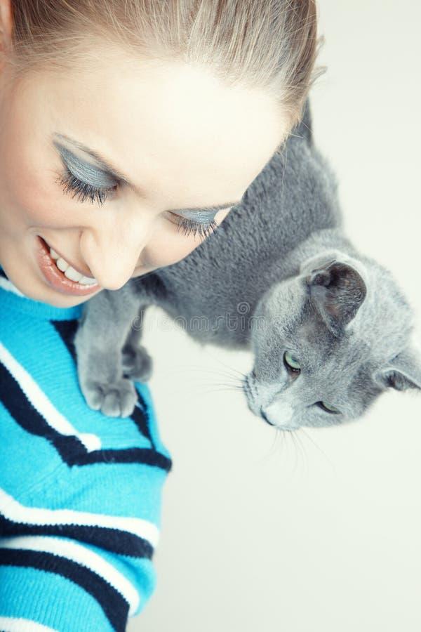 En dam och hennes katt som tycker om en fridsam eftermiddag royaltyfri foto