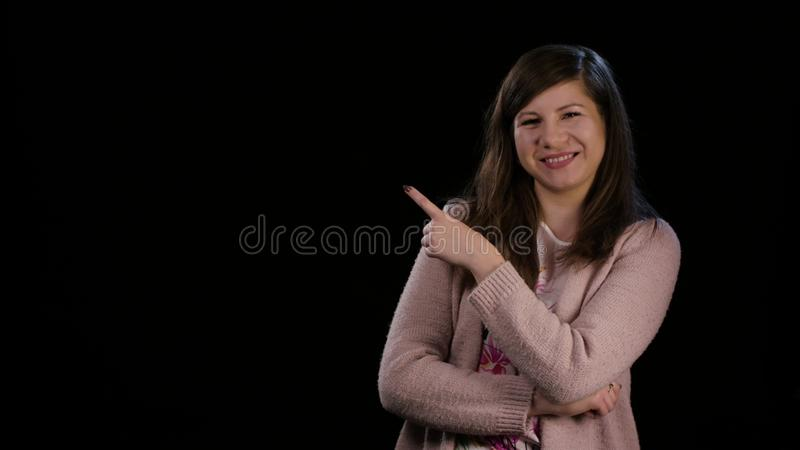 En dam Poiting ett finger mot en svart bakgrund royaltyfri foto