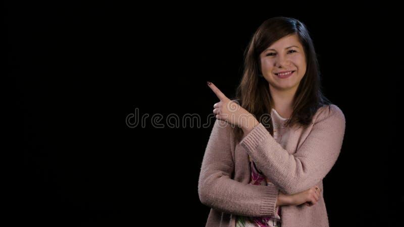 En dam Poiting ett finger mot en svart bakgrund royaltyfria foton