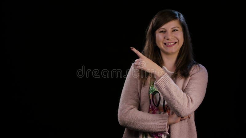 En dam Poiting ett finger mot en svart bakgrund fotografering för bildbyråer