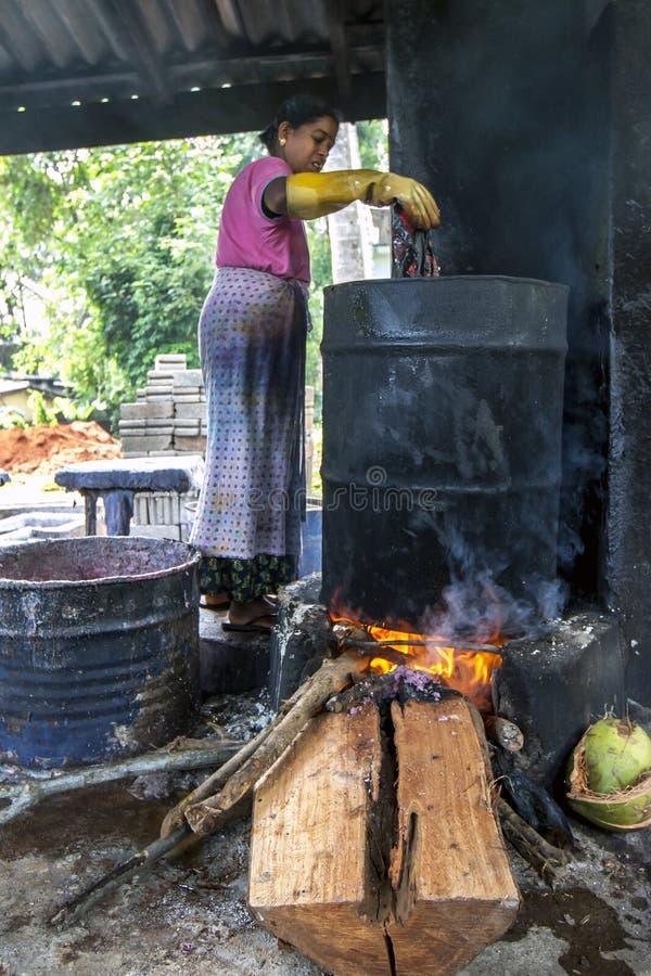 En dam smälter vaxet av en batik på den Baba Batik fabriken i Matale i Sri Lanka royaltyfri bild
