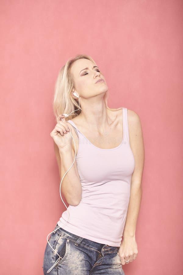 En dans f?r ung kvinna till musik som lyssnar p? h?rlurar som tycker om riktigt den med hennes st?ngda ?gon, royaltyfri bild