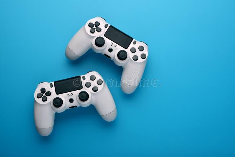 En dataspelkonkurrens Dobbelbegrepp Två vita styrspakar på blå bakgrund kopiera avst?nd Top besk?dar royaltyfri fotografi