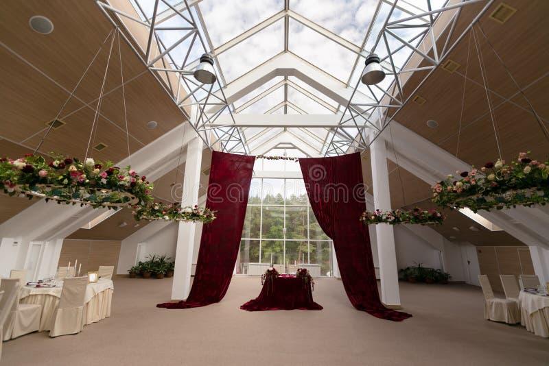 En dekorerad korridor i burgundy tonar för en bröllopceremoni med en dekorerad tabell av bruden och brudgummen arkivbild