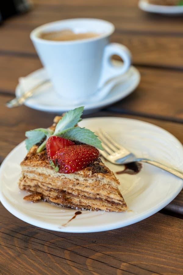 En dekorerade kopp kaffe och stycke av honungsockerkakan med jordgubbar och mintkaramellen på en trätabell arkivfoto