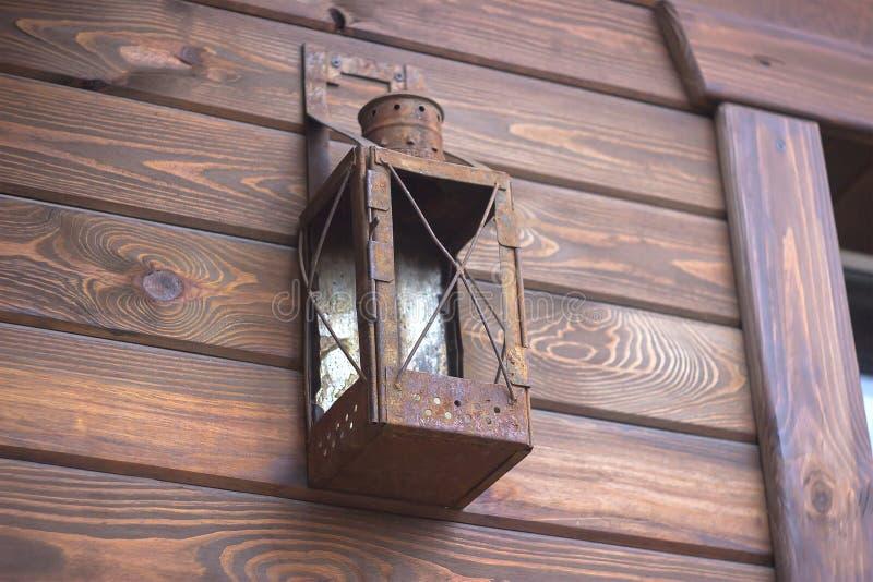 en den gammal lampa hänger på ett trähus arkivbilder