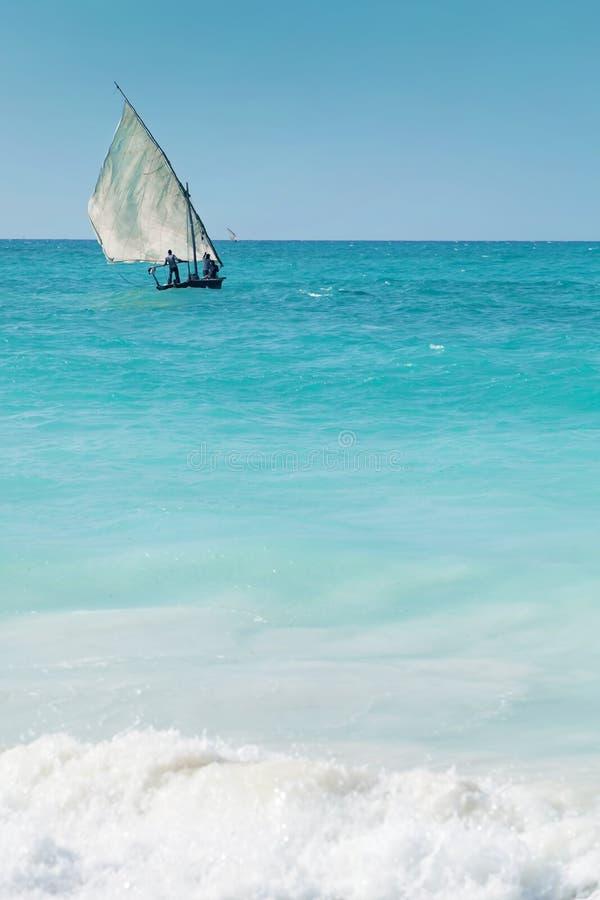 En dhow som seglar av in i horisonten på ett blått hav royaltyfri foto