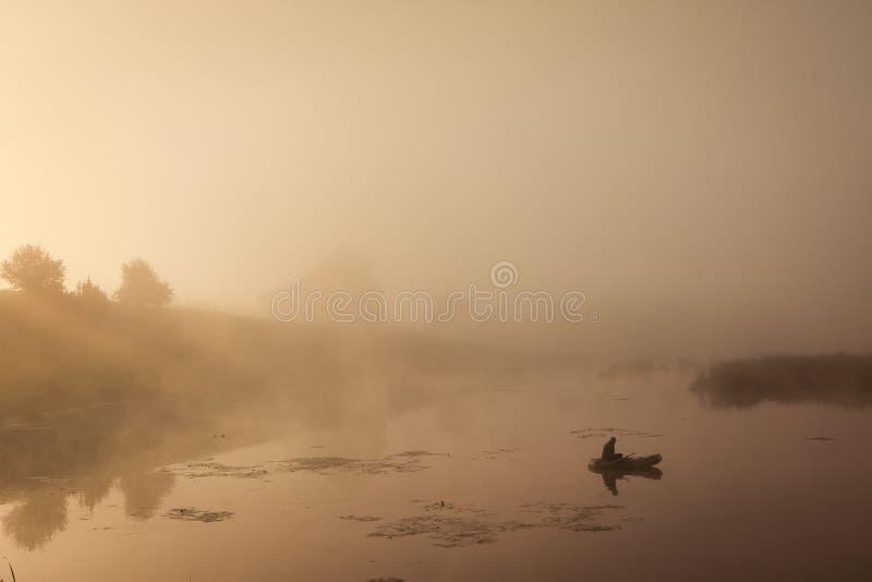 En dimmig morgon vid sjön Liten fiskebåt på sjön arkivfoton