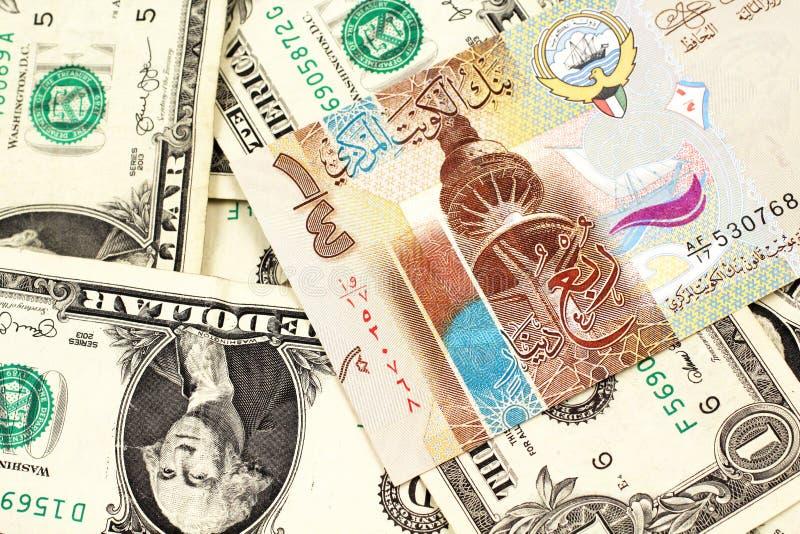En dinarsedel från Kuwait med amerikanen en dollar räkningar arkivfoto