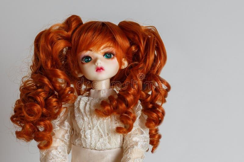 En docka med frodigt rött hår i en antik klänning royaltyfria foton