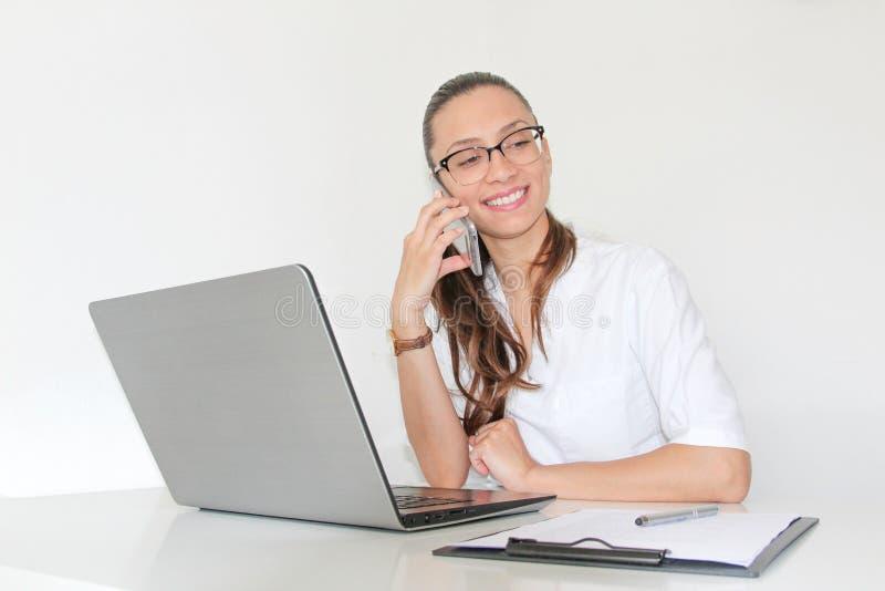 En doktor With för ung kvinna en bärbar dator i hennes kontor som talar på telefonen arkivbilder