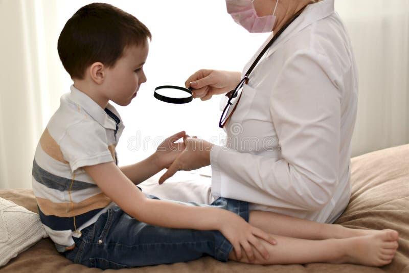En doktor med ett barn undersöker hennes händer till och med ett förstoringsglas arkivfoton