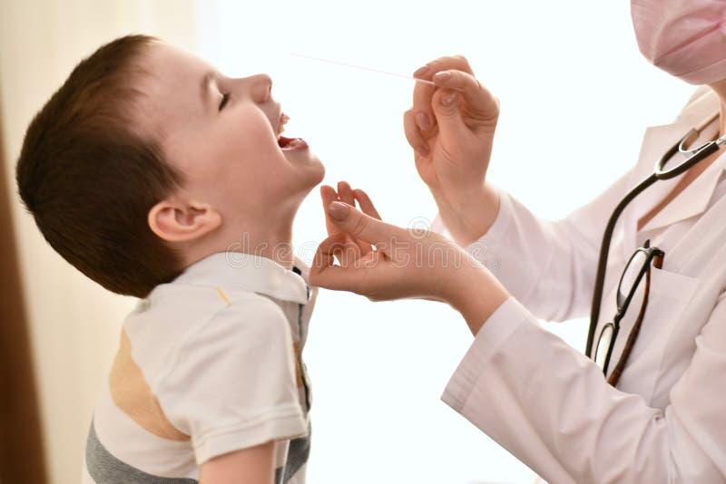 En doktor med en spatel skojar med ett barn royaltyfria foton