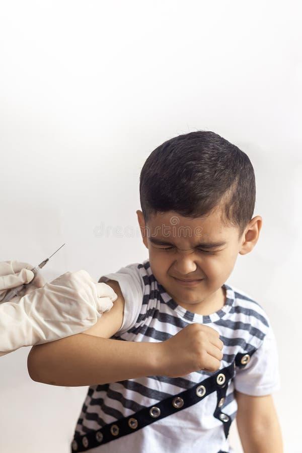 En doktor som vaccinerar den unga patienten Pys som skrämmas av injektion royaltyfria foton