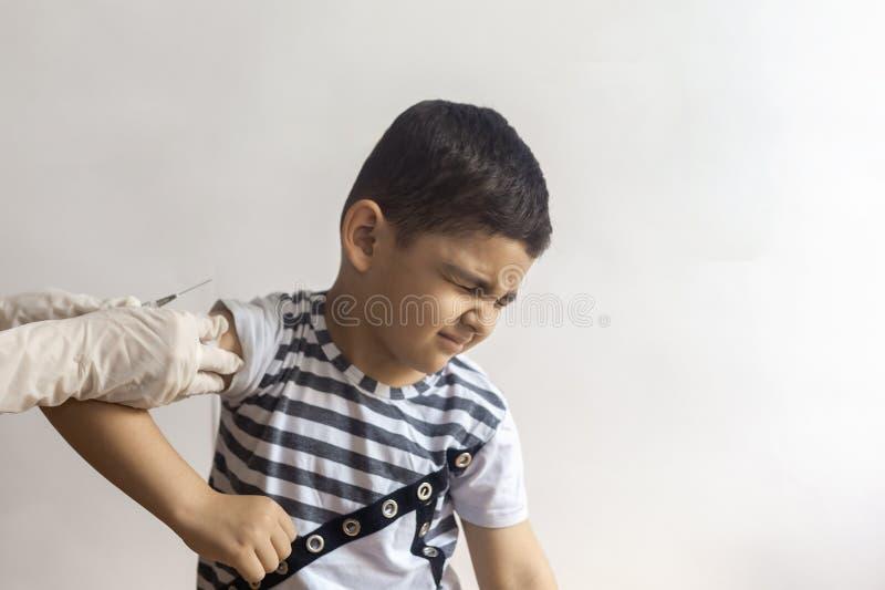 En doktor som vaccinerar den unga patienten Pys som skrämmas av injektion royaltyfri bild