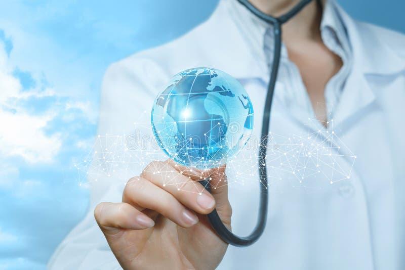 En doktor trycker på en ljus global översikt bak staketet av trådlösa anslutningar med hennes stetoskop arkivfoto