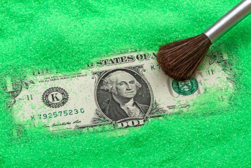 En dollar i den gröna sanden royaltyfri foto