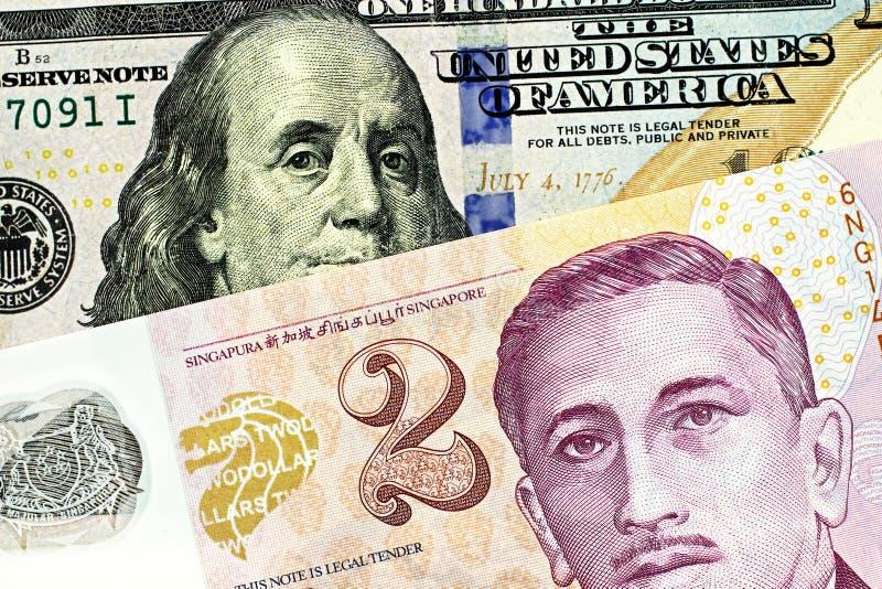 En dollarräkning för två Singapore med en ny amerikan hundra dollarräkning arkivfoto