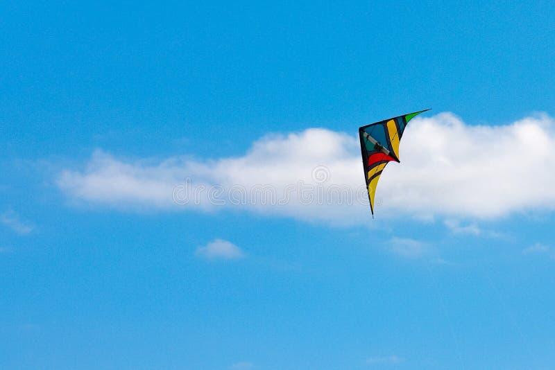 En drake mot blå himmel med små moln royaltyfri fotografi