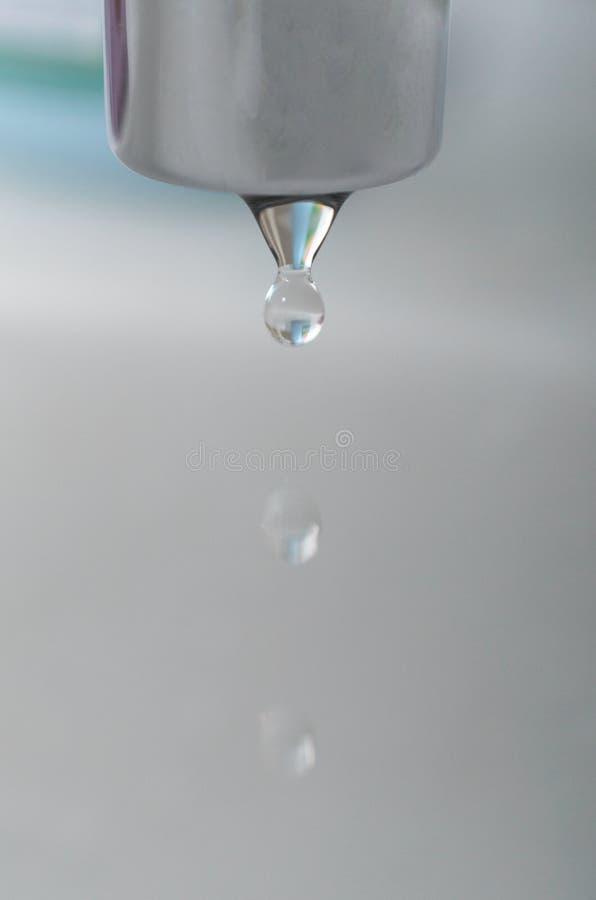 En droppe av vatten från klappet dryper i badrummet royaltyfri foto