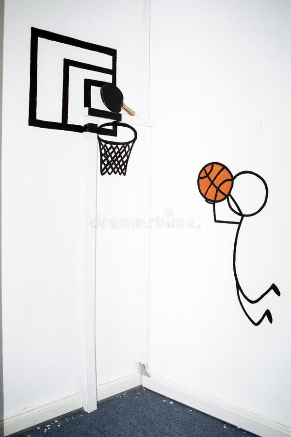En drunkning av en basketspelare och basketredet på en vägg i en barnskola royaltyfria foton